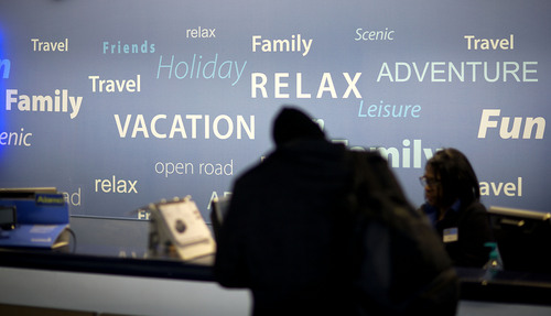A travel theme backdrop stands behind a rental car check-in counter as a customer rents a car at Hartsfield-Jackson Airport, Wednesday, Nov. 27, 2013, in Atlanta. More than 43 million people are to travel over the long holiday weekend, according to AAA. (AP Photo/David Goldman)