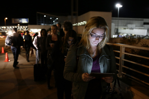 Tara Fitzsimons, a 20-year-old student who is traveling to Chicago, reads a book on her iPad while waiting in line to check in at the Los Angeles International Airport on Wednesday, Nov. 27, 2013, in Los Angeles. More than 43 million people are to travel over the long holiday weekend, according to AAA. (AP Photo/Jae C. Hong)