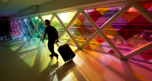 A lone traveler at the Miami International airport walks past a colorful art installation as he makes his way to the gate area, Tuesday, Nov. 26, 2013. A line of storms heading toward the Mid-Atlantic and East Coast packing ice, sleet and rain could upset holiday travel plans for Americans as they hit the road, skies and rails for Thanksgiving, causing a ripple effect of delays at some of the country's busiest airports. (AP Photo/J Pat Carter)
