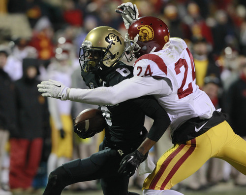 Colorado wide receiver Paul Richardson, left, is tackled after making a catch by USC safety Demetrius Wright in the fourth quarter of USC's 47-29 victory in an NCAA football game in Boulder, Colo., on Saturday, Nov. 23, 2013. (AP Photo/David Zalubowski)