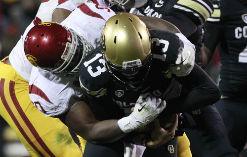 Colorado quarterback Sefo Liufau, front, is sacked by USC defensive end George Uko in the third quarter of USC's 47-29 victory in an NCAA football game in Boulder, Colo., on Saturday, Nov. 23, 2013. (AP Photo/David Zalubowski)