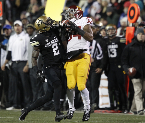 Southern California wide receiver Darreus Rogers, right, pulls in a pass as Colorado defensive back Kenneth Crawley covers in the first quarter of an NCAA college football game in Boulder, Colo., Saturday, Nov. 23, 2013. (AP Photo/David Zalubowski)