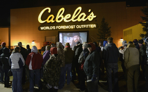 "Al Hartmann  |  The Salt Lake Tribune People lined up in front of Cabela's in Lehi Friday November 29 to enter the store at 5 a.m. when the doors open. Many received prizes for waiting in line.   Those towards the front of the line arrived on Thursday morning and camped out overnight.  To pass the time a giant screen shows the popular ""Duck Dynasty"" show."