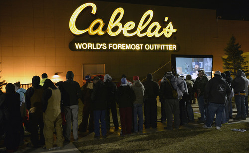 "Al Hartmann  |  The Salt Lake Tribune People lined up in front of Cabela's in Lehi Friday November 29 to enter the store at 5 a.m. when the doors open. Many received prizes for waiting in line.   Those towards the front of the line arrived on Thursday morning and camped out overnight. .  To pass the time a giant screen shows the popular ""Duck Dynasty"" show."