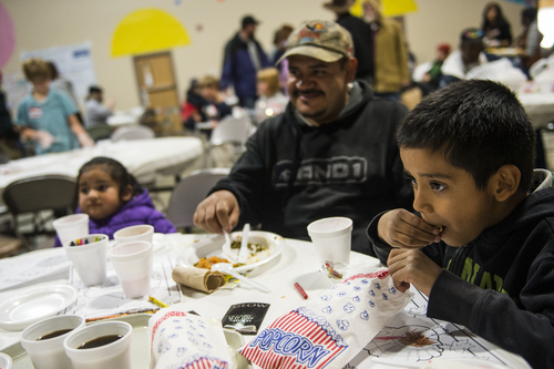 Chris Detrick  |  The Salt Lake Tribune The Fernandez family, Uriel Jr., 7, Uriel, and Lisbeth, 2, eat dinner at The Christian Life Center in Salt Lake City Thursday November 28, 2013. Salt Lake City Mission Public Relations manager Brad Jaques said they will serve over 2,000 people on Thanksgiving Day, which is also their 20th anniversary.