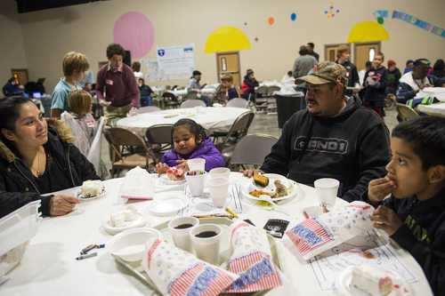 Chris Detrick  |  The Salt Lake Tribune The Fernandez family, Uriel Jr., 7, Uriel, Lisbeth, 2, and Ana eat dinner at The Christian Life Center in Salt Lake City Thursday November 28, 2013. Salt Lake City Mission Public Relations manager Brad Jaques said they will serve over 2,000 people on Thanksgiving Day, which is also their 20th anniversary.