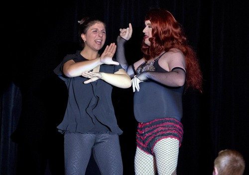 In this Nov. 22, 2013, photo, Holly Maniatty, left, an American Sign Language interpreter, signs during a performance by a contestant in the the Royal Majesty Drag Show and Competition in Portland, Maine. The 33-year-old has become an Internet sensation for the energetic way she uses dance moves, body language and American Sign Language to bring musical performances alive for those who can't hear. (AP Photo/Robert F. Bukaty)