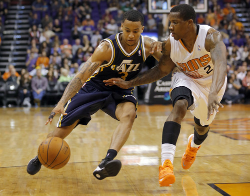 Utah Jazz guard Trey Burke (3) drives past Phoenix Suns guard Eric Bledsoe during the second half of an NBA basketball game on Saturday, Nov. 30, 2013, in Phoenix. (AP Photo/Matt York)