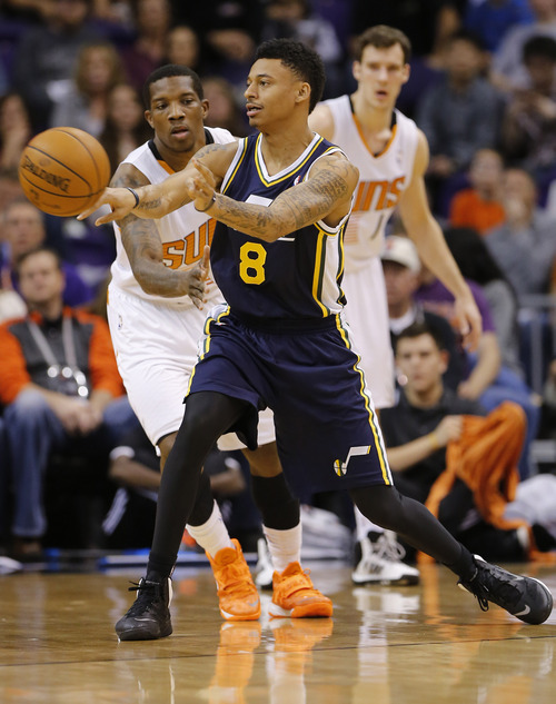 Utah Jazz guard Diante Garrett (8) passes as Phoenix Suns guard Eric Bledsoe, left, and Goran Dragic, of Slovenia, look on during the first half of an NBA basketball game on Saturday, Nov. 30, 2013, in Phoenix. (AP Photo/Matt York)