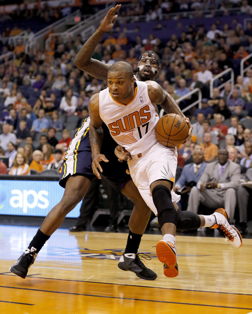 Phoenix Suns guard P.J. Tucker (17) drives past Utah Jazz forward Marvin Williams during the first half of an NBA basketball game on Saturday, Nov. 30, 2013, in Phoenix. (AP Photo/Matt York)