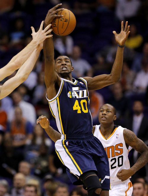 Utah Jazz forward Jeremy Evans (4) pulls down a long rebound as Phoenix Suns guard Archie Goodwin (20) looks on during the first half of an NBA basketball game on Saturday, Nov. 30, 2013, in Phoenix. (AP Photo/Matt York)