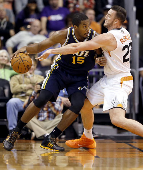 Utah Jazz center Derrick Favors (15) backs down Phoenix Suns center Miles Plumlee during the first half of an NBA basketball game on Saturday, Nov. 30, 2013, in Phoenix. (AP Photo/Matt York)