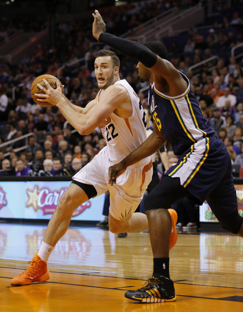 Phoenix Suns center Miles Plumlee (22) drives against Utah Jazz forward Derrick Favors during the first half of an NBA basketball game on Saturday, Nov. 30, 2013, in Phoenix. (AP Photo/Matt York)