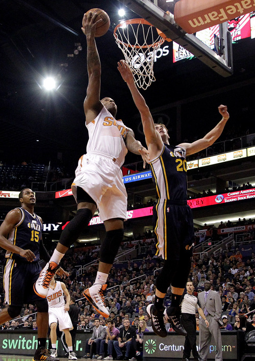 Phoenix Suns guard P.J. Tucker, left, shoots over Utah Jazz guard Gordan Hayward (20) during the first half of an NBA basketball game on Saturday, Nov. 30, 2013, in Phoenix. (AP Photo/Rick Scuteri)