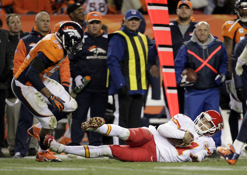 Kansas City Chiefs quarterback Alex Smith (11) slides to avoid a hit by Denver Broncos middle linebacker Wesley Woodyard (52) in the fourth quarter of an NFL football game, Sunday, Nov. 17, 2013, in Denver. (AP Photo/Joe Mahoney)