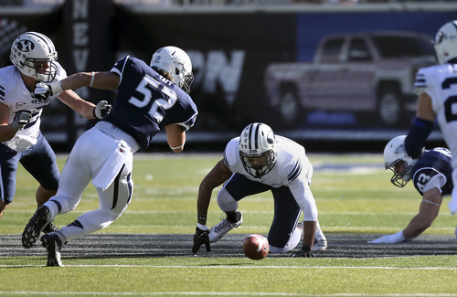 BYU's Cody Hoffman, center, and Nevada's Trevor Taft (52) scramble to recover a fumble during the first half an NCAA college football game in Reno, Nev., on Saturday, Nov. 30, 2013. (AP Photo/Cathleen Allison)
