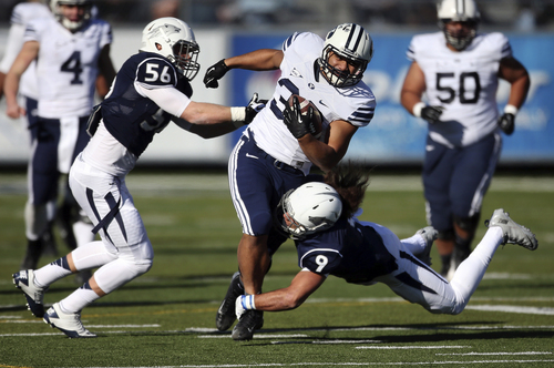BYU's Paul Lasike, center, tries to run through Nevada's Alex Bertrando (56) and Matthew Lyons (9) during the first half an NCAA college football game in Reno, Nev., on Saturday, Nov. 30, 2013. (AP Photo/Cathleen Allison)