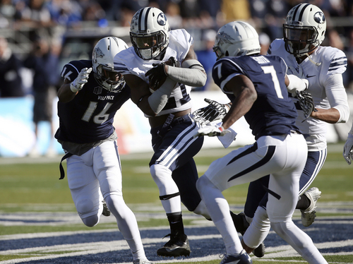 BYU's Jamaal Williams, second from left, tries to run through Nevada's Kaodi Dike (16) and Markus Smith (7) during the first half of an NCAA college football game in Reno, Nev., on Saturday, Nov. 30, 2013. (AP Photo/Cathleen Allison)