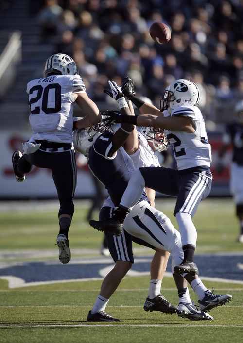 Nevada's Brandon Wimberly (1) tries to catch a pass while being surrounded BYU's Craig Bills (20), Daniel Sorensen, back, and Mike Hague (32) during the first half of an NCAA college football game in Reno, Nev., on Saturday, Nov. 30, 2013. (AP Photo/Cathleen Allison)