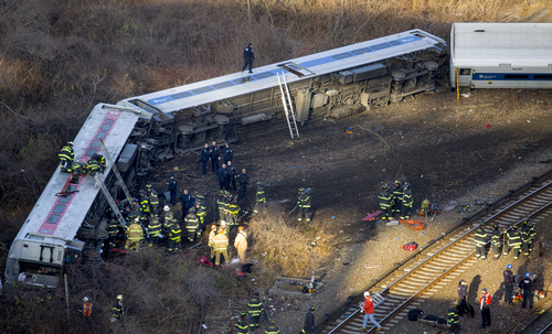 First responders gather at the derailment of a Metro-North passenger train in the Bronx borough of New York Sunday, Dec. 1, 2013. The train derailed on a curved section of track in the Bronx on Sunday morning, coming to rest just inches from the water and causing multiple fatalities and dozens of injuries, authorities said. Metropolitan Transportation Authority police say the train derailed near the Spuyten Duyvil station. (AP Photo/Craig Ruttle)