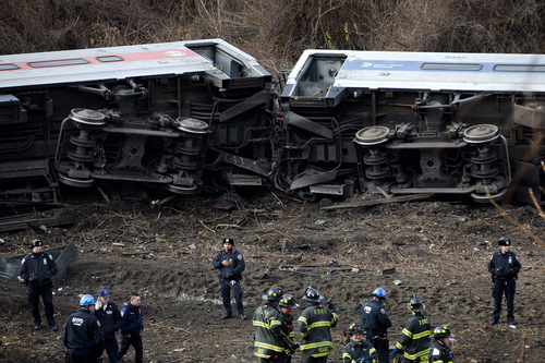 Emergency personnel respond to the scene of a Metro-North passenger train derailment in the Bronx borough of New York Sunday, Dec. 1, 2013. The train derailed on a curved section of track in the Bronx on Sunday morning, coming to rest just inches from the water and causing multiple fatalities and dozens of injuries, authorities said. Metropolitan Transportation Authority police say the train derailed near the Spuyten Duyvil station. (AP Photo/Craig Ruttle)
