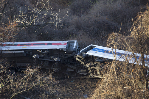 """Passenger cars are on their side after a Metro-North train derailed in the Bronx on Sunday morning, Dec. 1, 2013 causing """"multiple injuries,"""" authorities said. Metropolitan Transportation Authority police say the train derailed near the Spuyten Duyvil station. (AP Photo/Craig Ruttle)"""