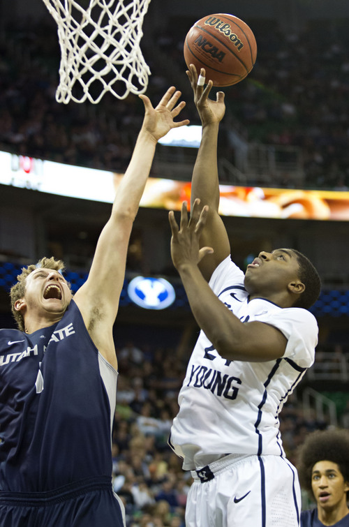 Lennie Mahler  |  The Salt Lake Tribune BYU's Frank Bartley IV scores over Utah State's Ben Clifford in the first half of their game at EnergySolutions Arena in Salt Lake City, Saturday, Nov. 30, 2013.