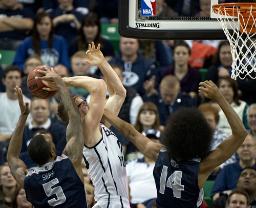 Lennie Mahler  |  The Salt Lake Tribune BYU's Erik Mika draws a foul from Utah State's Jalen Moore as Jarred Shaw helps on defense in the second half of their game at EnergySolutions Arena in Salt Lake City, Saturday, Nov. 30, 2013.