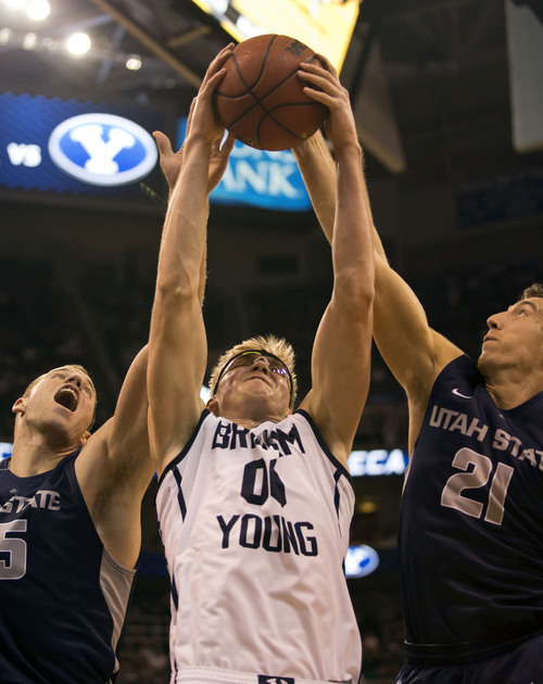 Lennie Mahler  |  The Salt Lake Tribune BYU's Erik Mika pulls in a rebound over Utah State's Jordan Stone and Spencer Butterfield in the second half of their game at EnergySolutions Arena in Salt Lake City, Saturday, Nov. 30, 2013.