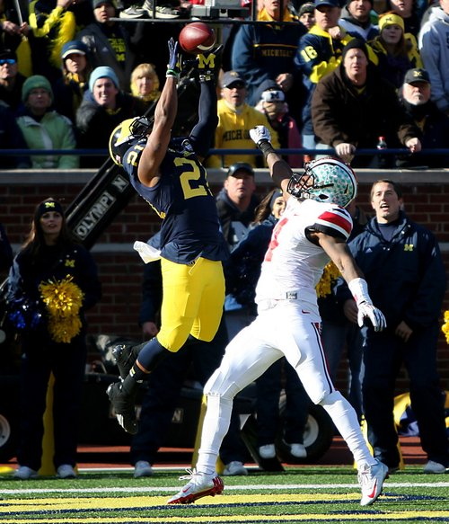Michigans' Jeremy Gallon catches touchdown pass against Ohio States' C.J. Barnett during the first quarter of an NCAA college football game Saturday, Nov. 30, 2013 at Michigan Stadium in Ann Arbor, Mich. (AP Photo/Detroit Free Press,  Kirthmon F. Dozier) DETROIT NEWS OUT;  NO SALES, MANDATORY CREDIT