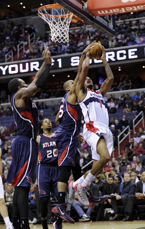 Washington Wizards forward Trevor Ariza (1) goes to the basket against Atlanta Hawks center Al Horford (15), Cartier Martin (20) and Paul Millsap, left, during the second half of an NBA basketball game, Saturday, Nov. 30, 2013, in Washington. The Wizards won 108-101. (AP Photo/Nick Wass)
