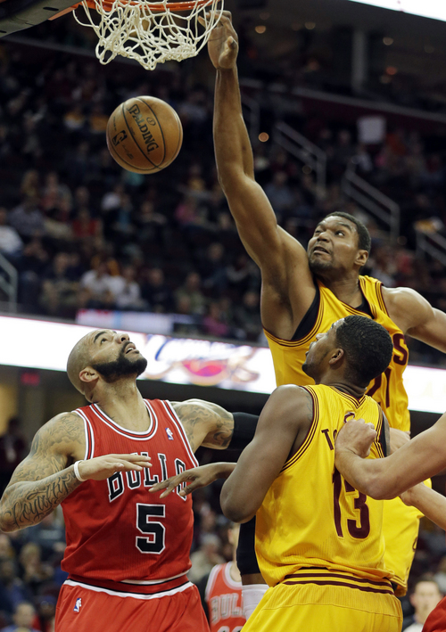 Cleveland Cavaliers' Andrew Bynum, top right, dunks on Chicago Bulls' Carlos Boozer (5) in the first quarter of an NBA basketball game Saturday, Nov. 30, 2013, in Cleveland. (AP Photo/Mark Duncan)