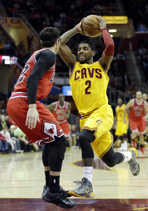 Cleveland Cavaliers' Kyrie Irving (2) drives the lane against Chicago Bulls' Kirk Hinrich in the fourth quarter of an NBA basketball game Saturday, Nov. 30, 2013, in Cleveland. Irving scored 19 points in Cleveland's 97-93 win. (AP Photo/Mark Duncan)
