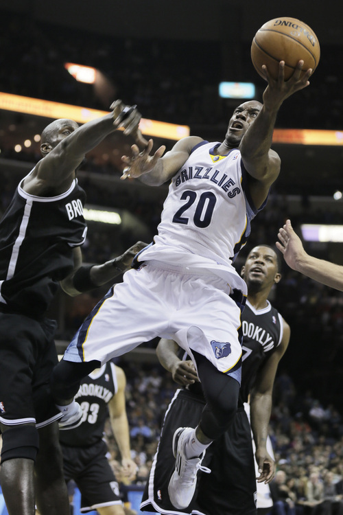 Memphis Grizzlies' Quincy Pondexter (20) goes to the basket between Brooklyn Nets' Kevin Garnett, left, and Joe Johnson, right, in the second half of an NBA basketball game in Memphis, Tenn., Saturday, Nov. 30, 2013. The Nets defeated the Grizzlies 97-88. (AP Photo/Danny Johnston)