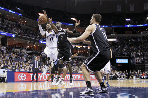 Memphis Grizzlies' Mike Conley (11) goes to the basket in front of Brooklyn Net's Kevin Garnett (2) and Brook Lopez (11) in the second half of an NBA basketball game in Memphis, Tenn., Saturday, Nov. 30, 2013. The Nets defeated the Grizzlies 97-88. (AP Photo/Danny Johnston)
