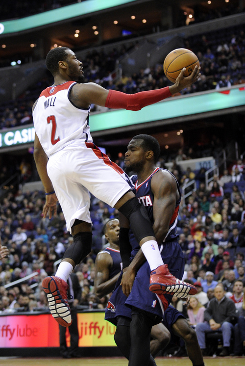 Washington Wizards guard John Wall (2) goes to the basket against Atlanta Hawks forward Paul Millsap, right, during the second half of an NBA basketball game, Saturday, Nov. 30, 2013, in Washington. Milsap was called for a foul on the play. The Wizards won 108-101. (AP Photo/Nick Wass)