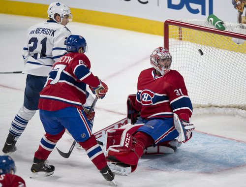 Montreal Canadiens goalie Carey Price stops a shot as teammate Max Pacioretty and Toronto Maple Leafs' James van Riemsdyk look on during the third period of an NHL hockey game Saturday, Nov. 30, 2013 in Montreal. The Canadiens beat the Leafs 4-2. (AP Photo/The Canadian Press, Paul Chiasson)