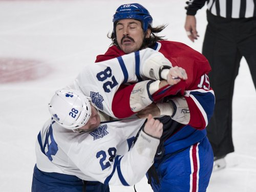 Montreal Canadiens' George Parros and Toronto Maple Leafs' Colton Orr square off during the second period of an NHL hockey game Saturday, Nov. 30, 2013 in Montreal. (AP Photo/The Canadian Press, Paul Chiasson)