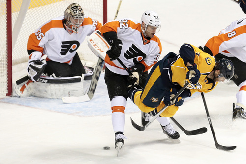 Nashville Predators forward Matt Cullen, right, shoots the puck backwards between the skates of Philadelphia Flyers defenseman Mark Streit (32), of Switzerland, in the second period of an NHL hockey game Saturday, Nov. 30, 2013, in Nashville, Tenn. Flyers goalie Steve Mason (35) guards the net. (AP Photo/Mark Humphrey)