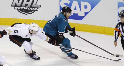 Anaheim Ducks' Ben Lovejoy and San Jose Sharks' Brad Stuart compete for the puck during the third period of an NHL hockey game, Saturday, Nov. 30, 2013, in San Jose, Calif. The Sharks won 4-3 in a shootout. (AP Photo/George Nikitin)