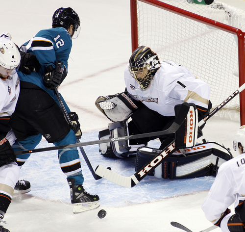 Anaheim Ducks goalie Jonas Hiller, right, blocks the puck in front of San Jose Sharks' Mike Brown during the first period of an NHL hockey game Saturday, Nov. 30, 2013, in San Jose, Calif. (AP Photo/George Nikitin)