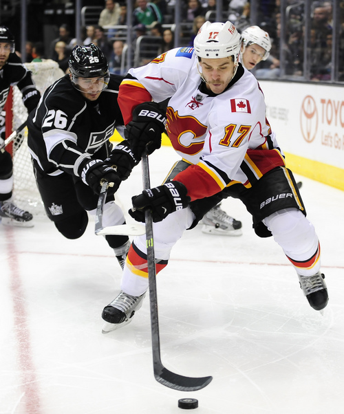 Calgary Flames left wing Lance Bouma (17) and Los Angeles Kings defenseman Slava Voynov (26), of Russia, reach for the puck during the third period of an NHL hockey game, Saturday, Nov. 30, 2013, in Los Angeles. The Flames won 2-1. (AP Photo/Gus Ruelas)