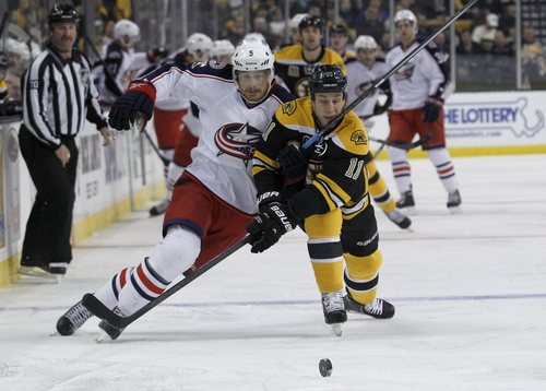 Columbus Blue Jackets right wing Jack Skille (5) and Boston Bruins center Gregory Campbell (11) vie for the puck during the first period of an NHL hockey game in Boston, Saturday, Nov. 30, 2013. (AP Photo/Mary Schwalm)