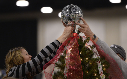 "Al Hartmann  |  The Salt Lake Tribune Jeanie Earl and John Olson put a disco ball on top of the second grade's ""Rock the Halls"" tree from Eagle Crest Elementary School in Lehi at the South Towne Exposition Center in Sandy Monday morning December 2.  It is for the Festival of Trees event to raise money for Primary Children's Medical Center.  All trees will be finished tonight by 7 p.m.  The festival will be open to the public on Wednesday starting at 10 a.m."