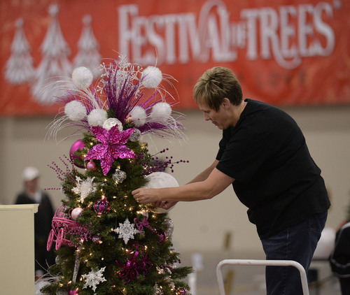 Al Hartmann  |  The Salt Lake Tribune Jodi Nuffer puts the finishing ornaments on a tribute tree at the South Towne Exposition Center in Sandy Monday morning December 2 for the Festival of Trees event to raise money for Primary Children's Medical Center. She pitched in with fellow employees of the Allstate Insurance claims office in Murray. The festival will be open to the public on Wednesday starting at 10 a.m.