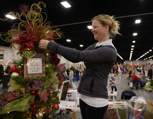 Al Hartmann  |  The Salt Lake Tribune Sara Watkins finishes decorating a family tree in tribute to relatives that have passed away in the Hattie Mae Pilcher family at the South Towne Exposition Center in Sandy Monday morning December 2.  It is for the Festival of Trees event to raise money for Primary Children's Hospital.  All trees will be finished tonight by 7 p.m.  The festival will be open to the public on Wednesday starting at 10 a.m.