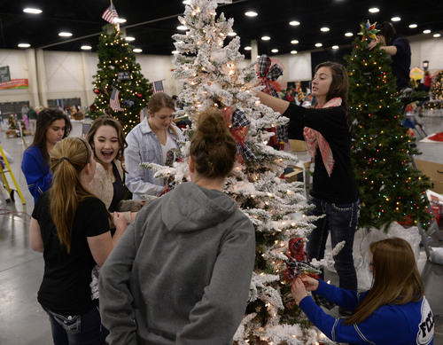 "Al Hartmann  |  The Salt Lake Tribune Bingham High School members of the Family Career Community Leaders of America decorate their ""Memory Lane"" tree at the South Towne Exposition Center in Sandy Monday morning December 2.  It is for the Festival of Trees event to raise money for Primary Children's Medical Center.  The festival will be open to the public on Wednesday starting at 10 a.m."