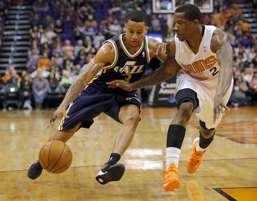 Utah Jazz guard Trey Burke (3) drives past Phoenix Suns guard Eric Bledsoe during the second half of an NBA basketball game on Saturday, Nov. 30, 2013, in Phoenix. (AP Photo/Matt York)