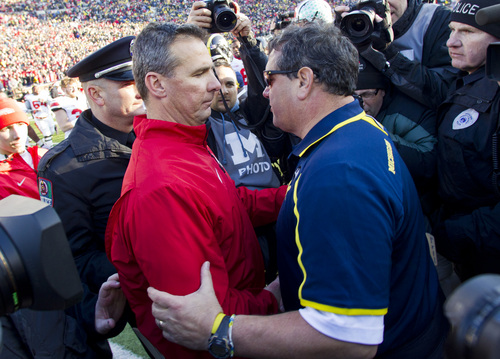 Ohio State head coach Urban Meyer, left, shares a handshake and hug with Michigan head coach Brady Hoke, right, after an NCAA college football game in Ann Arbor, Mich., Saturday, Nov. 30, 2013. Ohio State won 42-41. (AP Photo/Tony Ding)