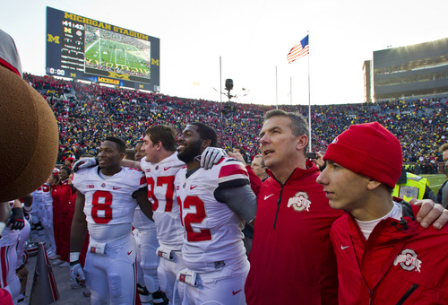 Ohio State head coach Urban Meyer, second from right, stands with his son Nathan, right, and his players in singing the school song after an NCAA college football game against Michigan in Ann Arbor, Mich., Saturday, Nov. 30, 2013. Ohio State won 42-41. (AP Photo/Tony Ding)